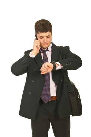 one to one meeting: Serious business man speaking by phone mobile and checking time isolated on white background