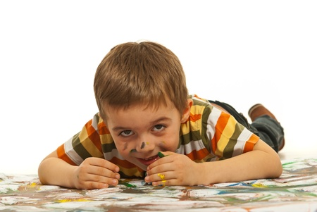 Messy happy boy trying to hide and laying down on painted background Stock Photo - 12596707