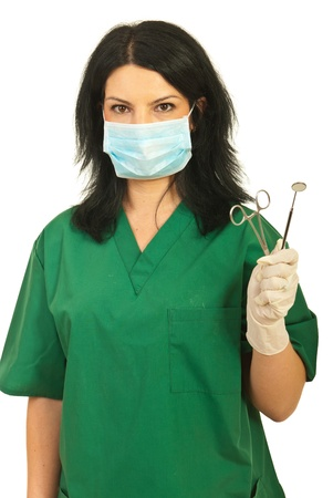 Dentist woman with protective mask holding forceps and dental mirror isolated on white background photo