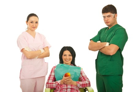 Smiling patient woman on chair holding apple in the middle of dentist team isolated on white background photo