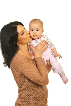 Madre che tiene e baciare la sua bambina isolata su sfondo bianco
