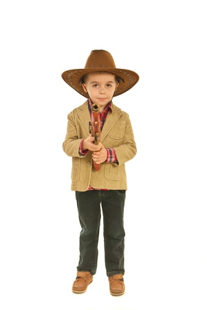 Full length of little cowboy holdign weapon toy isolated on white background photo