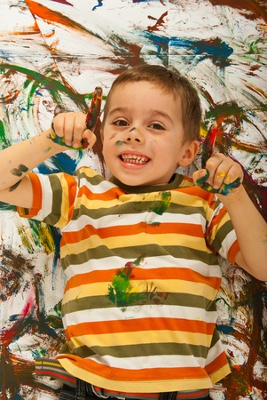 Happy messy boy lying down on painted background and pointing up isolated on white background Stock Photo - 12596849