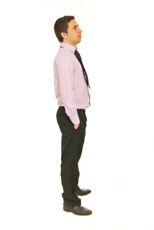 side shot: Full length of business man standing in profile with hands in pockets pants and looking away isolated onw hite background