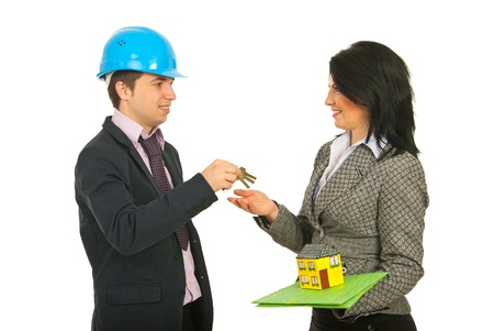 Architect giving keys to homeowner woman isolated onw hite background photo