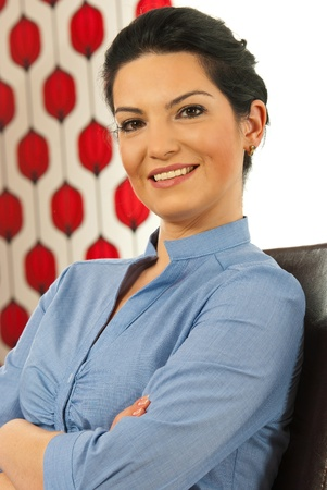 folded hands: Happy executive woman sitting on chair with arms folded in a modern office
