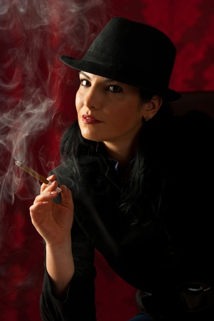 smoking cigar: Retro woman in black clothes with soft smile smoking in the night