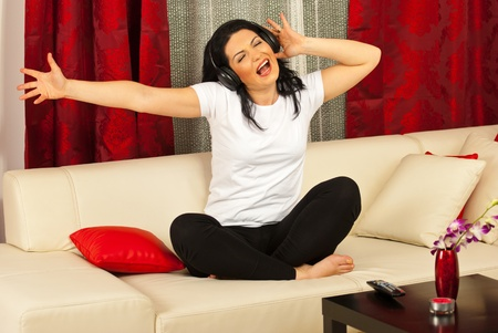 Woman singing and  listening music in headphones ,gesticulate with her hands and sitting with legs crossed on sofa in her living room photo