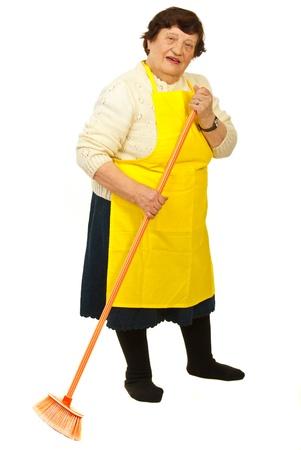 Lunghezza completa di donna anziana con casa gialla di pulizia grembiule con scopa isolato su sfondo bianco