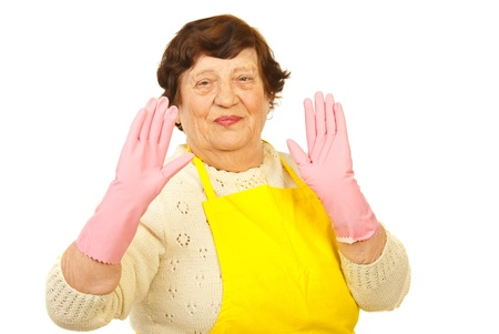 housewife gloves: Joyful elderly housewife  showing her palms in pink gloves isolated on white background