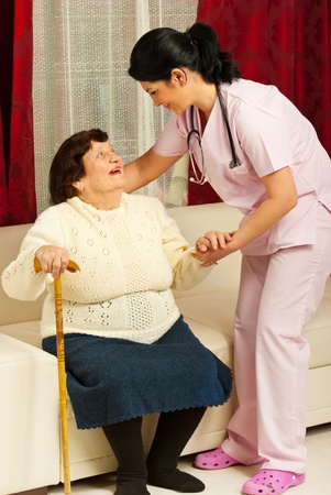 Nurse caring elderly woman and helping her to sit on couch at her home