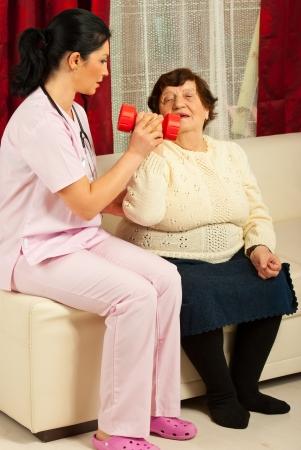 Infermiera aiuta donna senior e spiegare come fare esercizi di terapia a casa sua