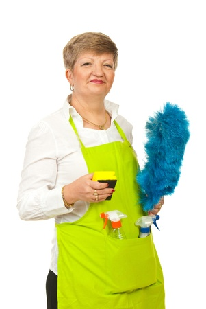housecleaning: Smiling mature housewife holding cleaning products isolated on white background Stock Photo