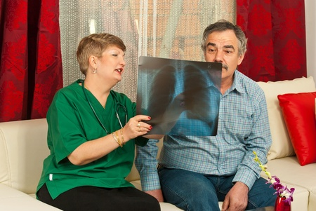 Doctor woman showing x-ray to surprised mature patient male in his home photo