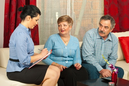 Consulente finanziario avendo una conversazione con coppia matura nella loro casa
