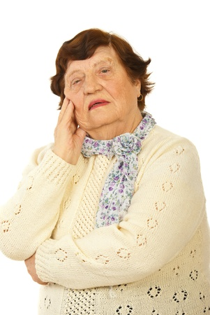 Worried senior woman holding hand to chin isolated on white background photo