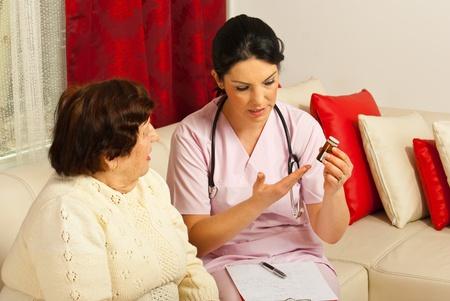 Arts die medicijnen en uitleg over het pillen nemen om bejaarde vrouw thuis