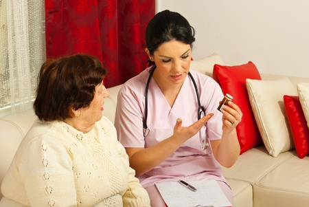 Doctor giving medicines and explaining how to take pills to elderly woman at home photo