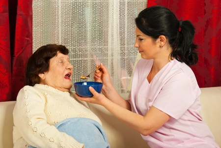 Nurse giving soup to sick elderly woman at home Stock Photo