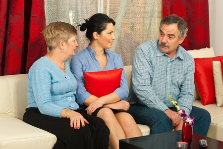 Mother and daughter having conversation with sad father in their home photo