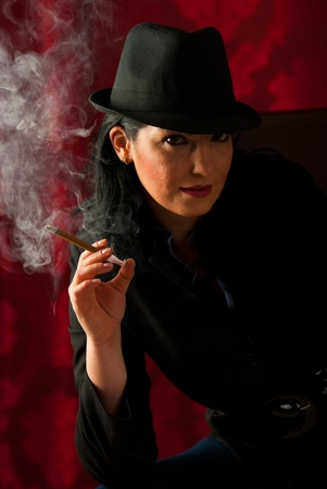 Beauty woman with retro hat smoking in the night photo