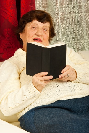 Senior woman sitting on couch and reading book in her home photo