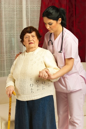 Nurse helping sick senior woman to walk  in her home photo