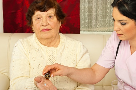 Nurse giving medicines to elderly woman patient in her home Stock Photo - 12922601