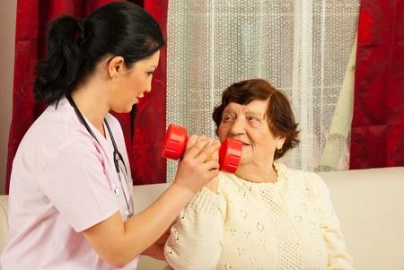 physical test: Terapeuta aiutando donna anziana a fare exercisies con manubri a casa Archivio Fotografico
