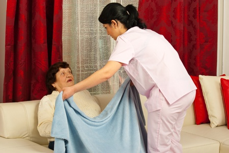 Nurse woman covering elderly woman with a blanket in her home Stock Photo - 12922580