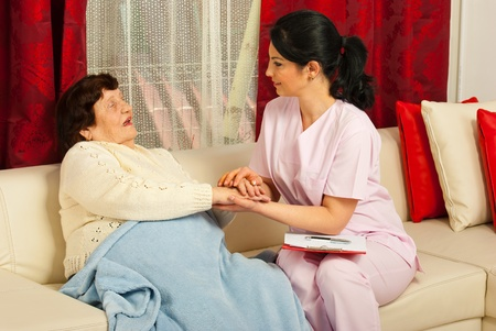 Nurse comforting sick elderly woman in her home Stock Photo - 12922581