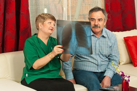 Doctor woman showing x-ray to senior man in his house photo