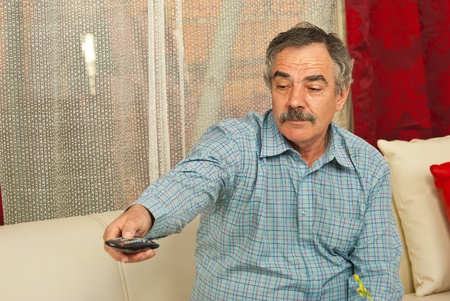 Senior man sitting on couch in living room and opening tv with remote control photo