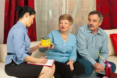 Real estate agent presenting a minaiture house to mature couple in their house photo
