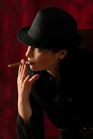 cigar smoking woman: Woman with hat smoking and looking to the light in night Stock Photo