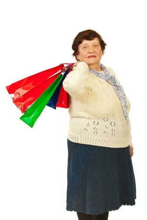 octogenarian: Elderly woman shopper holding shopping bags  on shoulder isolated on white background