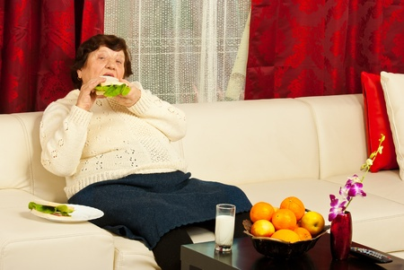 Elderly woman eating sandwich and sitting on couch in her home photo