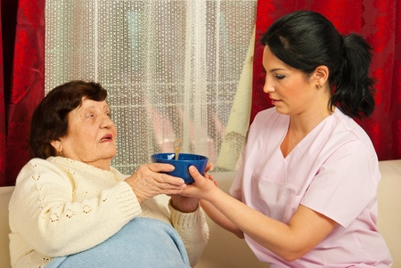 Nurse giving bowl with soup to senior woman  home Stock Photo - 12922384