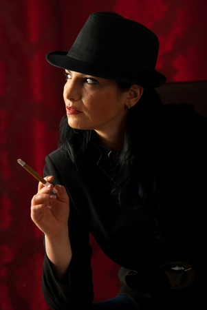 Quiet retro woman holding cigar and waiting in darkness photo