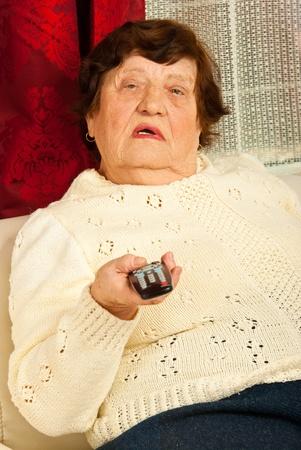 Donna anziana che tiene il telecomando e guardare la tv a casa
