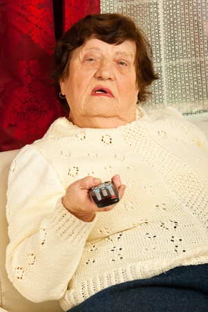 Elderly woman holding remote control and watching tv home