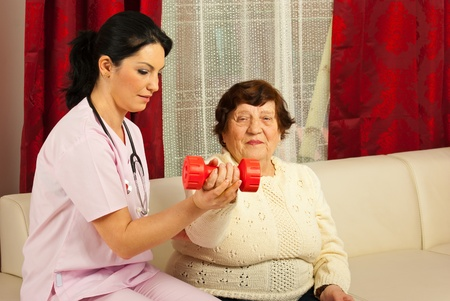 Therapist woman helping senior to do exercises with barbell home