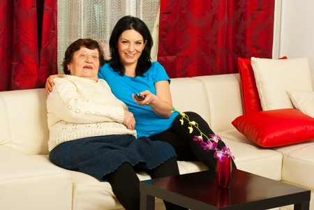 Grandma and adult granddaughter watch tv together in living room photo