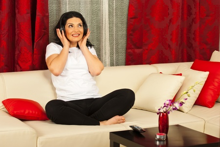 Happy woman sitting on couch in living room and listening music in headphones Stock Photo - 12922308