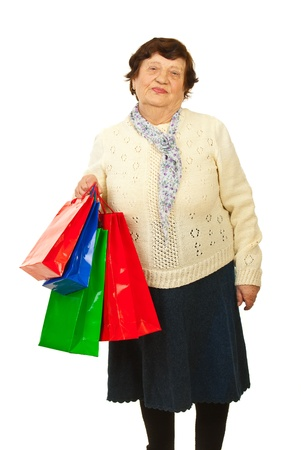 octogenarian: Senior woman holding colorful shopping bags isolated on white background