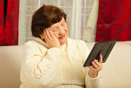 Sad elderly woman holding hand to face and looking at photo frame in her home photo