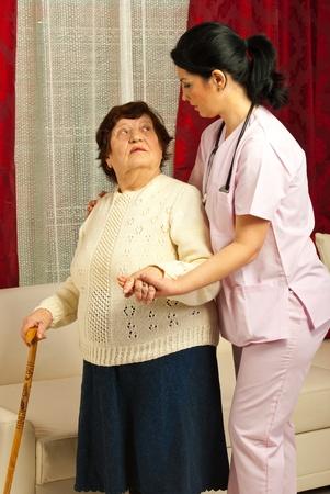 Verpleegster helpt bejaarde vrouw om te wandelen in haar huis Stockfoto