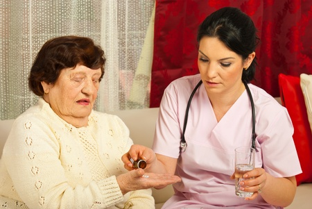 doctor giving pills: Doctor gives pills and water to senior woman patient in her home