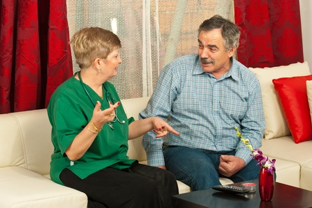 Doctor woman and senior man having conversation home photo