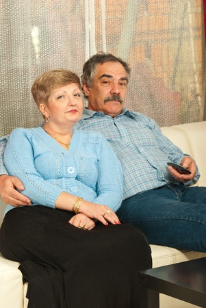 Middle aged couple watching tv home and sitting on couch photo